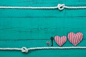 Blank blue wood sign with hearts, key and lock by rope with knots border