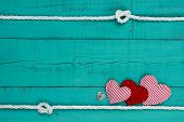 Red hearts and heart lock by rope border against teal blue wooden background