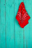 Red bandana hanging on blank antique teal blue wood door