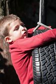 stock photo of tire swing  - child on swing made with car tire