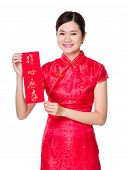 Woman with traditional cheongsam and holding Fai Chun, phrase meaning is everything going smoothly and easily