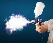 Painter with airbrush gun and white magical smoke concept