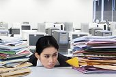 stock photo of boring  - Overworked businesswoman with many jobs looking at pile of documents with bored expression - JPG