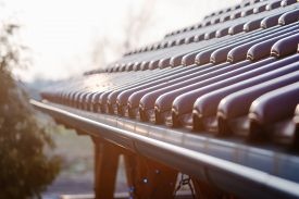 stock photo of red roof  - Tiled roof of wooden arbor with galvanized gutter  - JPG