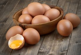 picture of fragile  - eggs in a wooden bowl on the table from the old boards broken egg shell and yolk - JPG