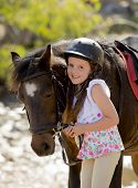stock photo of horse girl  - sweet beautiful young girl 7 or 8 years old holding bridle of little pony horse smiling happy wearing safety jockey helmet posing outdoors on countryside in summer holiday - JPG