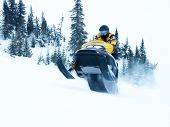 foto of winter sport  - ski doo going fast and jumping in winter - JPG