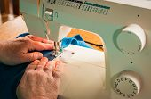 foto of stitches  - Soft blue fabric getting sewn up with a zigzag stitch. ** Note: Shallow depth of field - JPG