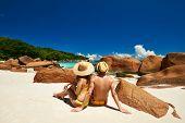 stock photo of couple sitting beach  - Couple sitting on a tropical beach at Seychelles - JPG