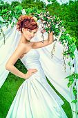 picture of wedding arch  - Beautiful bride with chaming red hair stands under the wedding arch - JPG