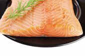 picture of fresh water fish  - raw fresh uncooked salmon red fish fillet on black plate with rosemary twig isolated over white background - JPG