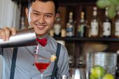 picture of bartender  - Cheerful young bartender filling glass with a cocktail - JPG