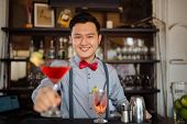 pic of bartender  - Portrait of smiling handsome bartender offering a cocktail - JPG