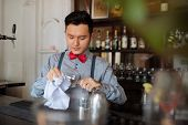 foto of bartender  - Young Vietnamese bartender wiping a wine glass - JPG