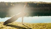 stock photo of  practices  - man practices asanas on yoga in harmony with the nature - JPG