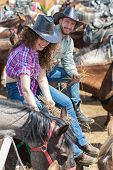 picture of feeding horse  - cowboy couple feeding horses hay in stable - JPG