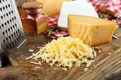 stock photo of grating  - Grated cheese on wooden cutting board - JPG