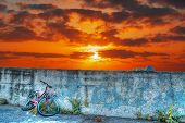 picture of wrecking  - old bike wreck against the wall at sunset - JPG
