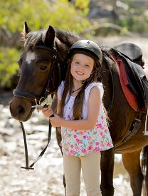 stock photo of year horse  - sweet beautiful young girl 7 or 8 years old holding bridle of little pony horse smiling happy wearing safety jockey helmet posing outdoors on countryside in summer holiday - JPG