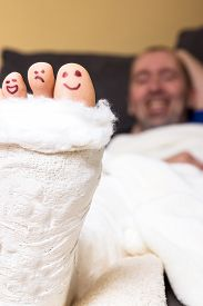 pic of painted toes  - Toes looking out the of a plaster painted with funny faces - JPG