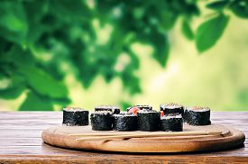 foto of photosynthesis  - Sushi on a wooden table with a natural green background - JPG