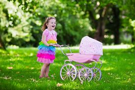 image of baby doll  - Little girl pushing toy stroller with bear - JPG
