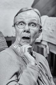 stock photo of matron  - Surprised senior matron woman looking at camera - JPG