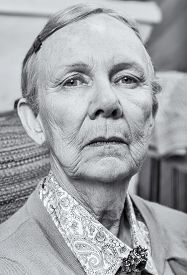 pic of matron  - Serious elderly lady in sweater looking down at camera - JPG