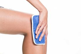 stock photo of hurt  - woman applying cold pack on swollen hurting knee - JPG