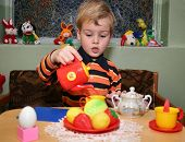 stock photo of nursery school child  - child play with dinner tea in kindergarten - JPG