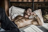 Shirtless sexy male model lying alone on his bed poster