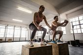 Muscular couple doing jumping squats in crossfit gym poster
