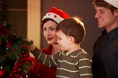 picture of nuclear family  - Family looking at christmas tree at home celebrating together - JPG