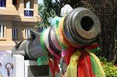 Ancient canon with colourful textiles in Thailand.