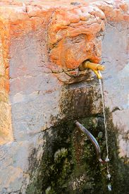 pic of tapping  - Public drinking water from a Italian fountain faucet in Verona - JPG