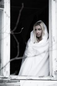 pic of wraith  - Beautiful young woman in a white sheet near the window - JPG