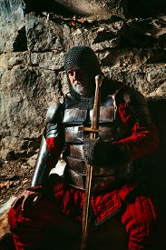 stock photo of sword  - Old medieval King in armor with sword is sitting on furs near the camp fire - JPG