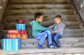 pic of adversity humor  - two brothers playfully trying to seize gift - JPG