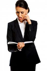 picture of irritated  - Irritated businesswoman reading her notes - JPG
