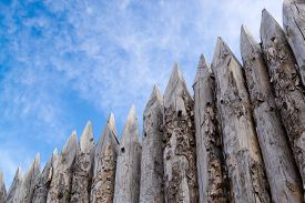 stock photo of stockade  - Wooden palisades form a defense barricade to stop intruders - JPG