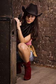 stock photo of gunfights  - The Beautiful sheriff woman on wall background - JPG