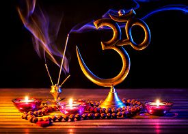 stock photo of om  - Om symbol incense smoke candle and japa mala on wooden table at black background - JPG