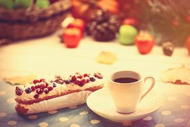 pic of eclairs  - Eclair and cup of coffee on wooden table - JPG