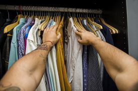 foto of pov  - Man searching for a shirt hanging on the rail in his wardrobe - JPG