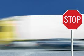 picture of truck-stop  - Red stop road sign motion blurred truck vehicle traffic in background regulatory warning signage octagon white octagonal frame metallic pole post - JPG