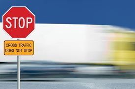 picture of truck-stop  - Red stop road sign motion blurred truck vehicle traffic in background regulatory warning signage octagon white octagonal frame metallic pole post yellow cross traffic does not stop text signage - JPG