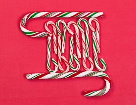 pic of peppermint  - Pattern of peppermint candy canes on red background - JPG