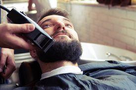 picture of barber razor  - barber shaving beard with electric razor in vintage barber shop - JPG
