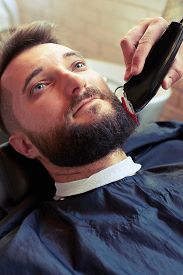 picture of barber razor  - barber shaving beard with electric razor of client in professional barbershop - JPG