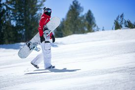 foto of snowboarding  - snowboarder holding  snowboard and climbs up the slope - JPG
